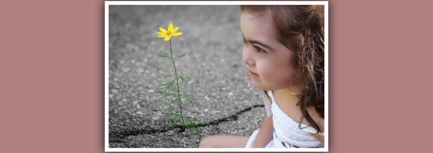 imagen nina con sindrome down mirando flor crece en la carretera