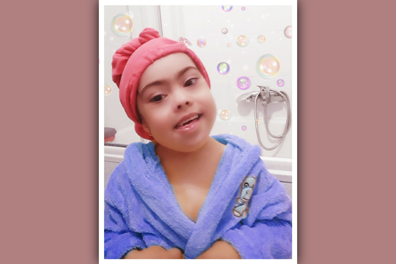 imagen de niña con sindrome de down en albornoz en su rutina de baño