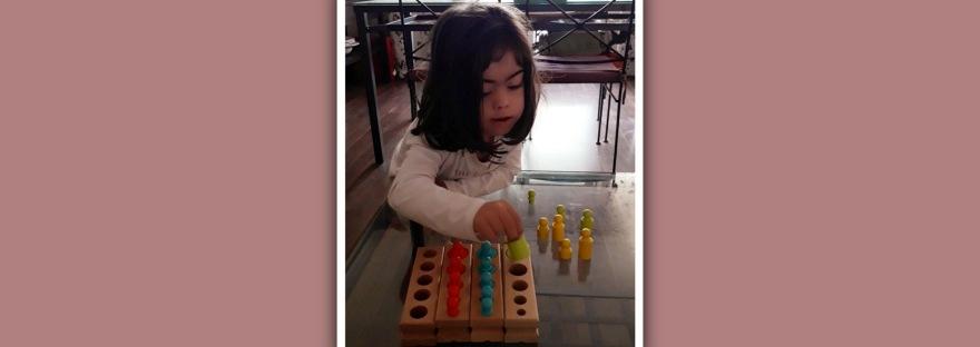 imagen niña sindrome de down con cilindros montessori