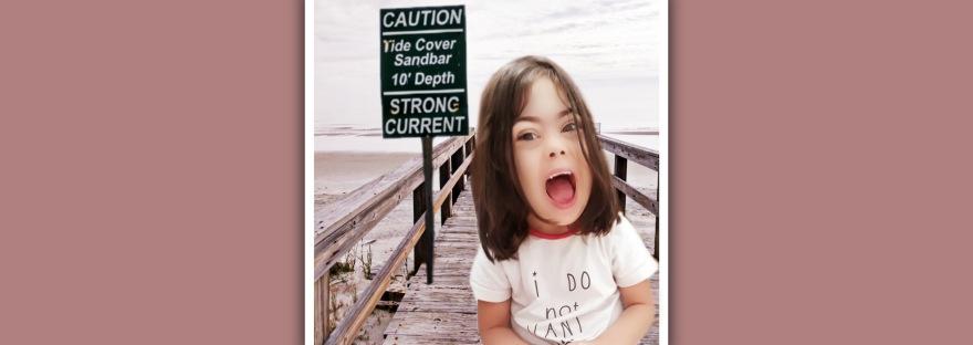 imagen niña sindrome de down en playa con cartel de precaucion