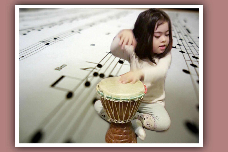 nina con sindrome de down tocando un djembe
