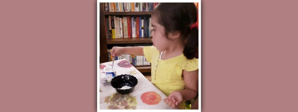 niña sindrome de down trasvasando un yogur