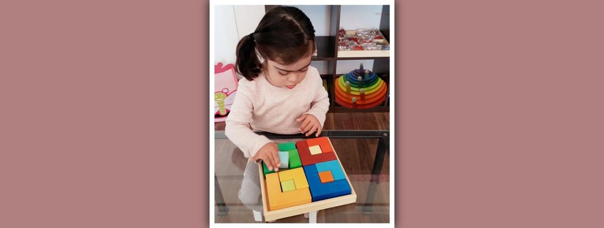 niña con sindrome de down haciendo puzzle Grimm