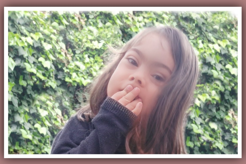 imagen de niña con sindrome de down tapandose la boca