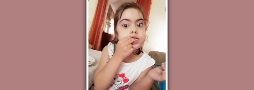 niña con sindrome de Down comiendo