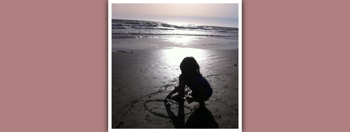 niña en la playa al atardecer dibujando un circulo en la arena