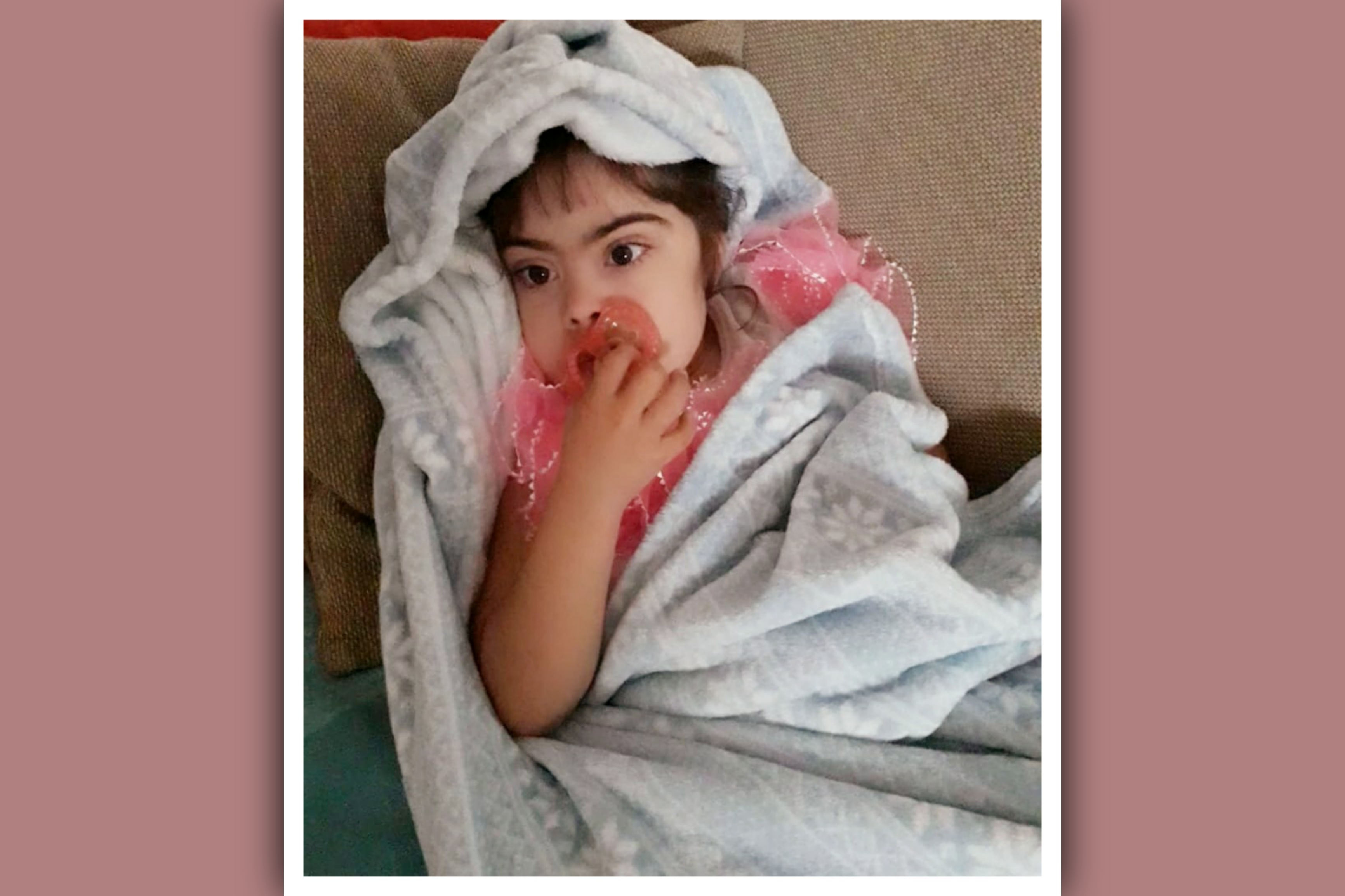 niña con síndrome de down con chupete y manta