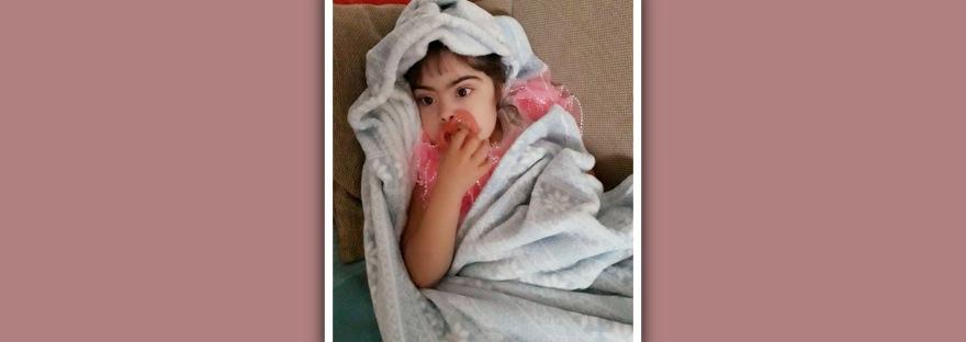niña con sindrome de down con chupete y manta