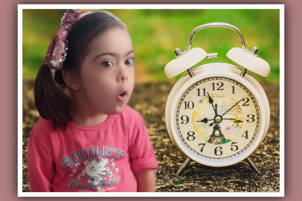 imagen de niña con sindrome de down y un reloj