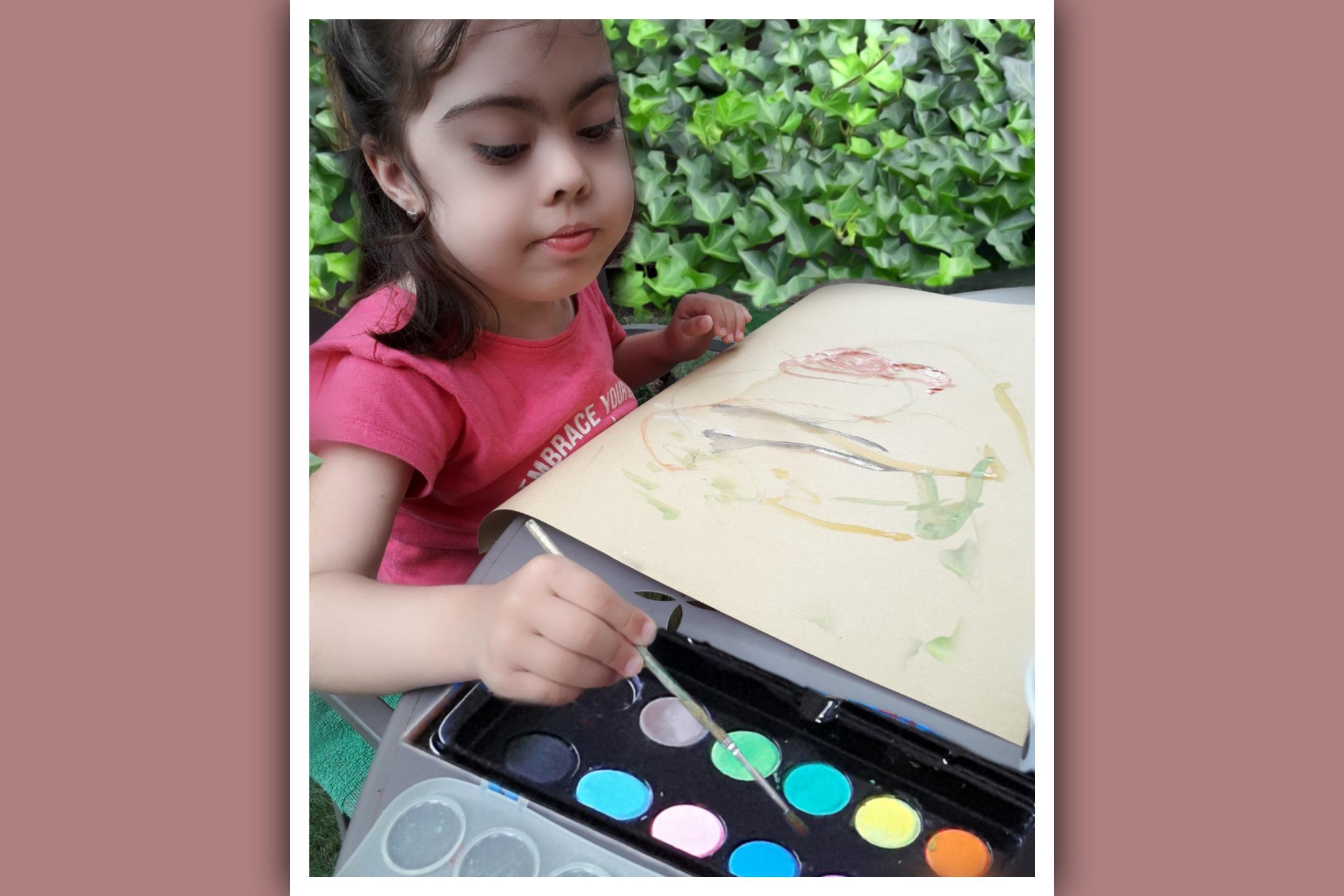 niña con sindrome de down pintando con acuarelas